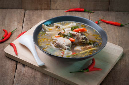 wooden floors: hot and chicken sour soup on wooden floors. Thai spicy food.