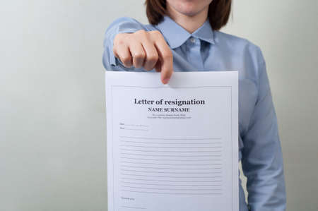 work wear: asian woman in work wear displaying resignation form. business concept.