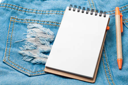 nicked: Notepad paper and pencil on blue jean texture.