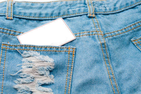 nicked: Old blue jeans and a copy space of greeting card on pocket and white background.