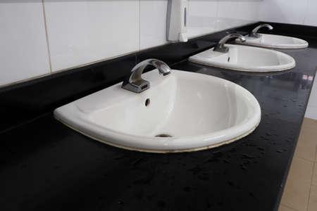 jabon liquido: caja de jabón líquido y sumideros de azulejos blancos en la sala de baño público.