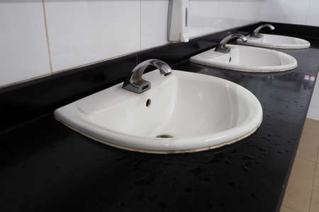 latrine: Liquid soap box and white tile sinks in public toilet room.