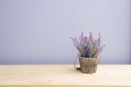Wood table with purple lavender flower on flower pot and  purple cement wall, Left copy space area. 版權商用圖片