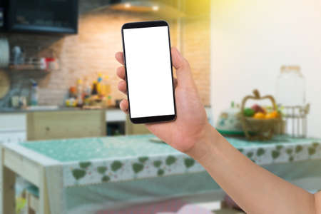 delivery room: human hand hold smart phone, tablet, cellphone with white blank screen on blurry Kitchen room Background, Online food delivery Concept.
