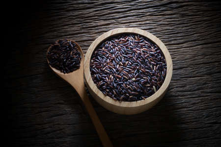 black rice: black grain of rice on wood table, Low key picture style. Stock Photo