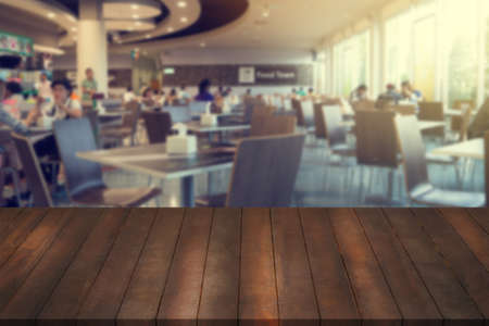 ledge: wooden table, mock up interior restaurant design, advertising food court with wooden table texture background, empty table ready for product display montage over blurred food court background.