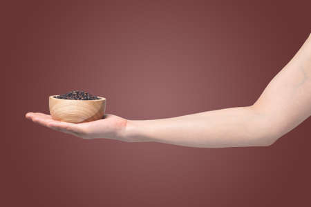 human hand holding  wooden plate with black rice grain  on isolated gradient red background.
