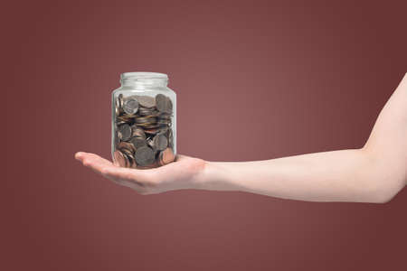 human hand hold piggy bank with bath coins on isolated gradient red background. Stock Photo