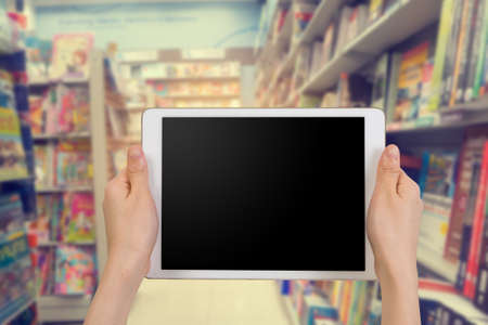 busines: human hand hold and touch blank screen smart phone, tablet, cellphone on blurry bookshelf in bookstore, Online shopping books Concept.