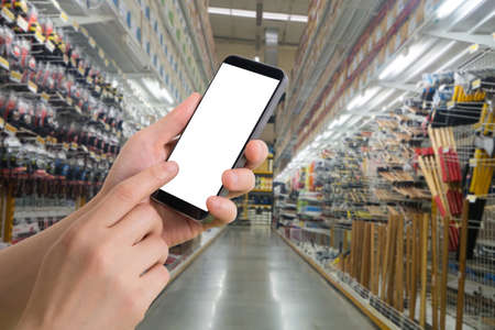 human hand hold smartphone, tablet, cell phone with blurry hardware store. concept of shopping and finding hardware tool for house repair.