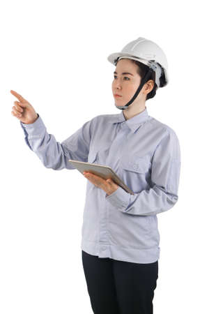 Asian Women wearing a helmet and protective clothing Checking the stock , Concept of working women in engineering. young woman holding tablet and pointing finger on isolated white background.