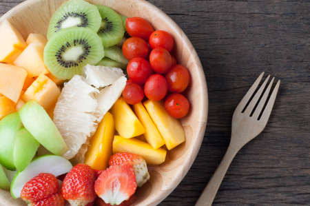 kitchen table with Variety of Fruits on wood plate and fork, group of Fruits salad - healthy eating and dieting food, concept of health care,  Image focus top view. Stock Photo