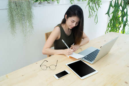 Office table with young asian woman writing on notepad paper, Asian woman working freelance at home workplace, Concept of young woman using laptop. Stock Photo