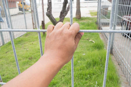 humans hand catching grille at restricted area, concept of prevention on private zone.