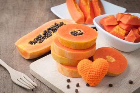 Table en bois avec tranche papaye mûre et orange signe de forme de coeur sur planche à découper en bois - une alimentation saine et régime alimentaire, concept de soins de santé. vue de dessus de table en bois. Banque d'images - 78440573