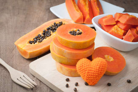 wood table with slice ripe papaya and orange heart shape sign on wood cutting board - healthy eating and dieting food, concept of health care. view from top wood table. Stock Photo
