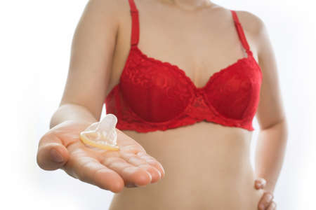 young asian woman in sexy red bra hold condom on isolated white background.