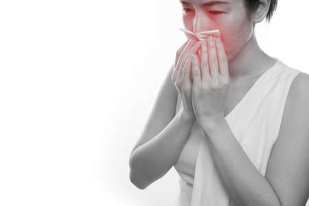 ail: young asian woman sneezing on isolated white background. concept of healthcare.