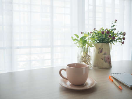 office table with hot coffee cup, beautiful flower on pot, notepad paper and pencil on blurry beautiful white drape window texture background.