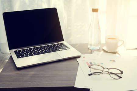 ビジネス情報紙、モダンなガラスのリビング ルームで白いドレープの熱いコーヒーとのオフィスのテーブル。
