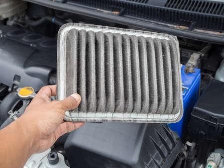 인간의 손에 더러운 공기 필터 자동차, 청소 및 공기 필터 검사의 개념을 개최하십시오.