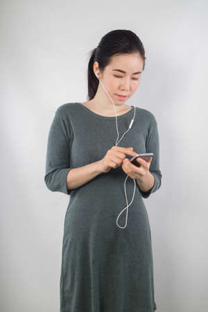 front view: young woman be pregnant in maternity clothes listening to music on cement wall background.