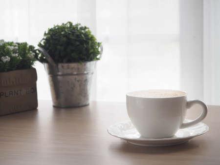 hölzerner Bürotisch mit Schale Lattekaffee und schöner Blume auf undeutlichem weißem Vorhangbeschaffenheitshintergrund, Ansicht von der vorderen hölzernen Tabelle.