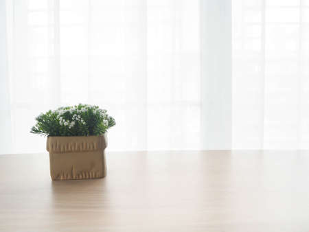 front view: wood office table with free copy space for text and beautiful white flower on pot on white drape texture background on sunny day. view from front  office table. Stock Photo