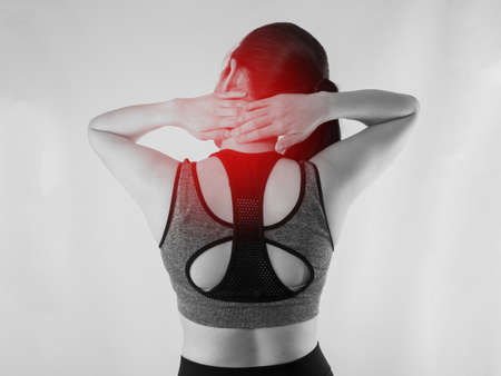 taint: Young Asian woman in workout cloth having Neck pain with red focus dot on isolated background. back view people.