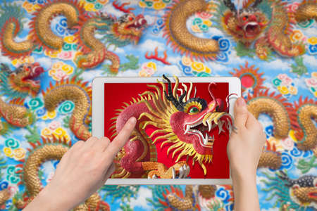 tradition: human hand hold smartphone, tablet, cell phone with big dragon statue come out screen. concept of celebrate Chinese New Year background , concept of the Year of the Dragon.