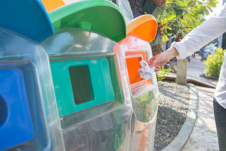human hand throwing  used paper into recycling bin at public park, concept of environmental protection Stock Photo