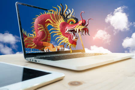 tradition: office table with red dragon on computer screen and cloud sky background.