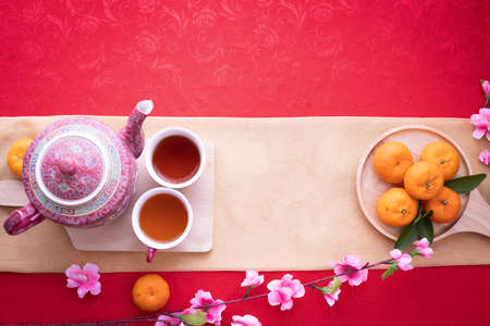 Orange fruit, Pink cherry blossom and teapot with Copy space for text on red texture background, Chinese new year background. top view.