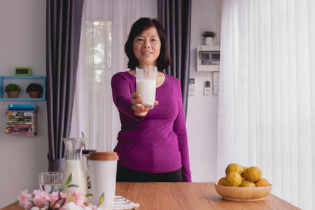 Breakfast table with Asian Elderly woman hold glass of milk at home, front view.