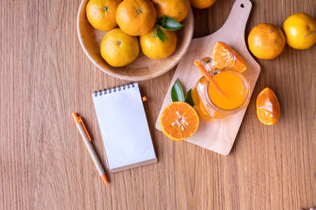 Cup of Cold Orange juice and blank screen on notepad paper on wood table, top table.