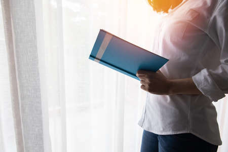 businesswoman reading a book, side view.