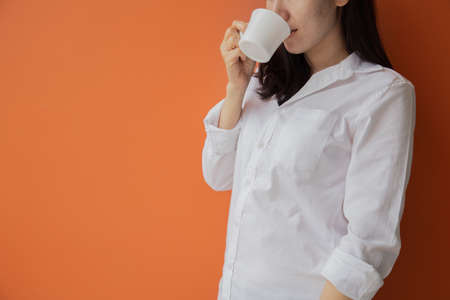 young asian woman drinking hot drink, coffee, tea on isolated orange background. concept of health care lifestyle.