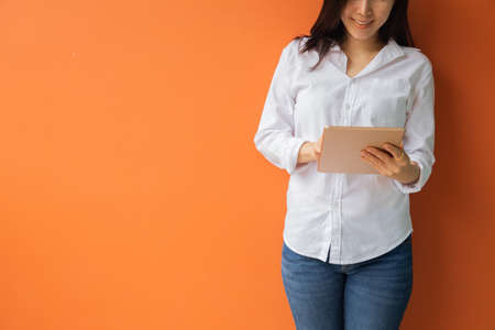 young asian woman using tablet, smartphone, cell phone on isolated orange background. concept of asian lifestyle.