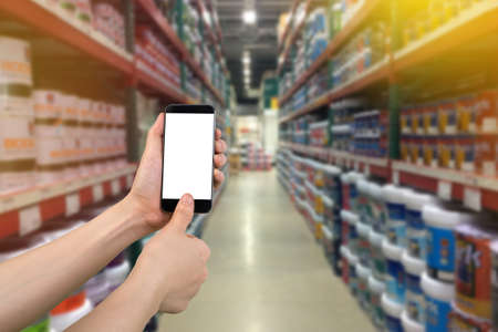 human hand scanning finger on smartphone with blurry product shelf. concept of shopping online.