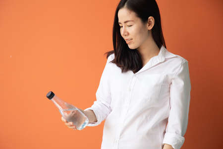 young asian woman holding bottle of water on isolated orange background.