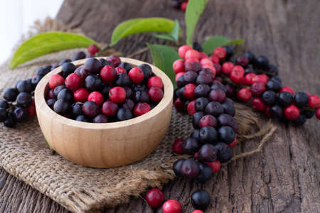 wood kitchen table with thai blueberries, traditional thai fruit.