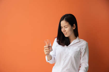 young asian woman drinking water on isolated orange background. concept of health care lifestyle.