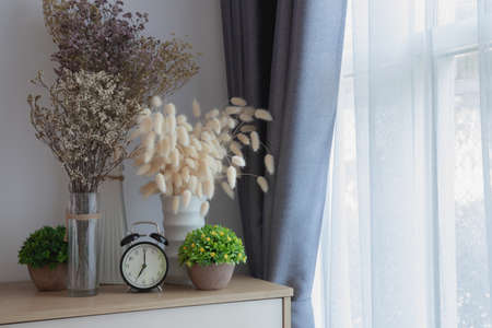 wood table with decoration flowers on white curtain window texture background, copy space.