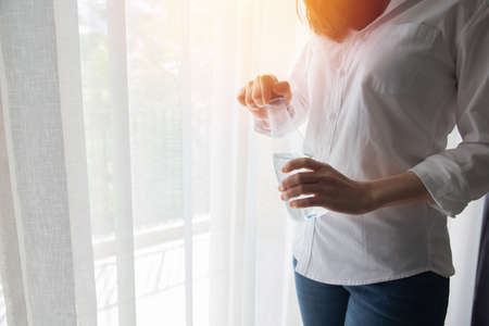 young woman drinking mineral water on white curtain windows texture background, concept of healthy care lifestyle.
