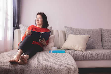 Beautiful girl at home sitting on the couch, reading a magazine and having a coffee break, relaxation concept.