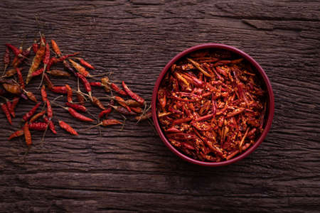 Kitchen table with dried chilli pepper, top view. Imagens