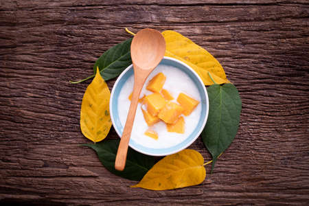 wood table with nutrition yogurt with topping sliced mangoes, dessert. Zdjęcie Seryjne