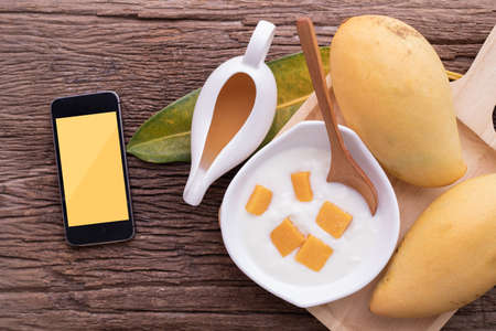 Copy space on smartphone with Mango yogurt and juice on wood table, top view, copy space.