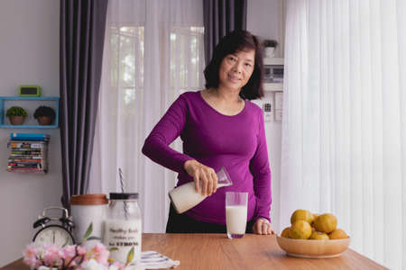 Asian Elderly woman pouring milk on kitchen table. breakfast table, front view. Zdjęcie Seryjne