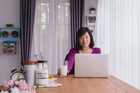 Breakfast table with Asian Elderly woman using laptop. front view.